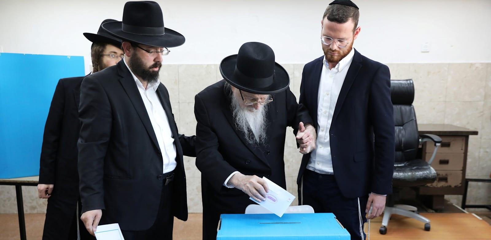 צעירים מהחברה החרדית עוזרים למבוגר להצביע בקלפי במאה שערים