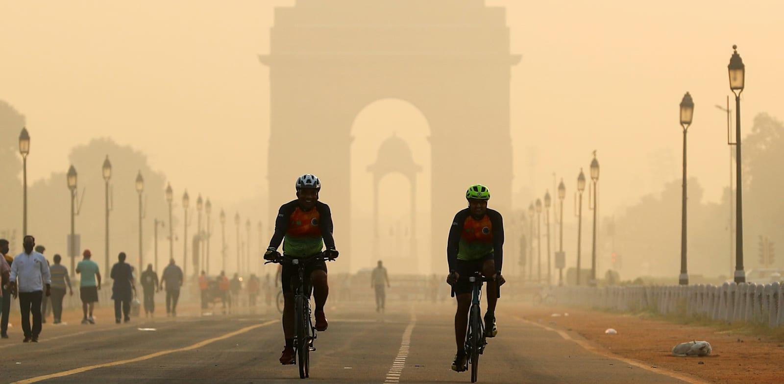 רוכבי אופניים בניו דלהי המזוהמת / צילום: Reuters, Adnan Abidi