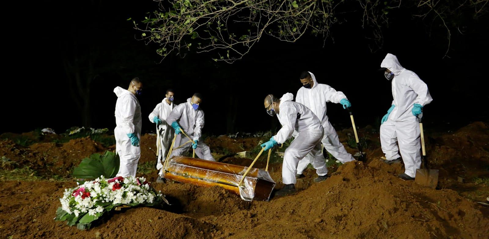עובדי בית הקברות בסאו פאולו קוברים מתים מנגיף הקורונה. מספר המתים כה גבוה שבבתי הקברות נאלצים להאריך את שעות העבודה עד הלילה / צילום: Associated Press, Nelson Antoine