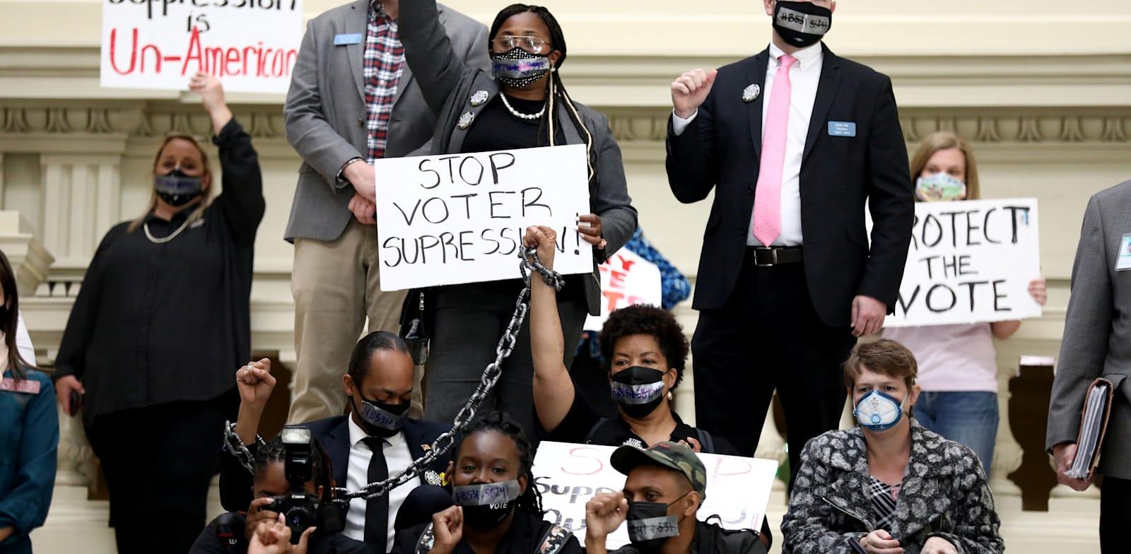 מוחים על מדרגות בית הנבחרים בג'ורג'יה נגד החוק שמגביל את ההצבעה, מרץ / צילום: Reuters, DUSTIN CHAMBERS