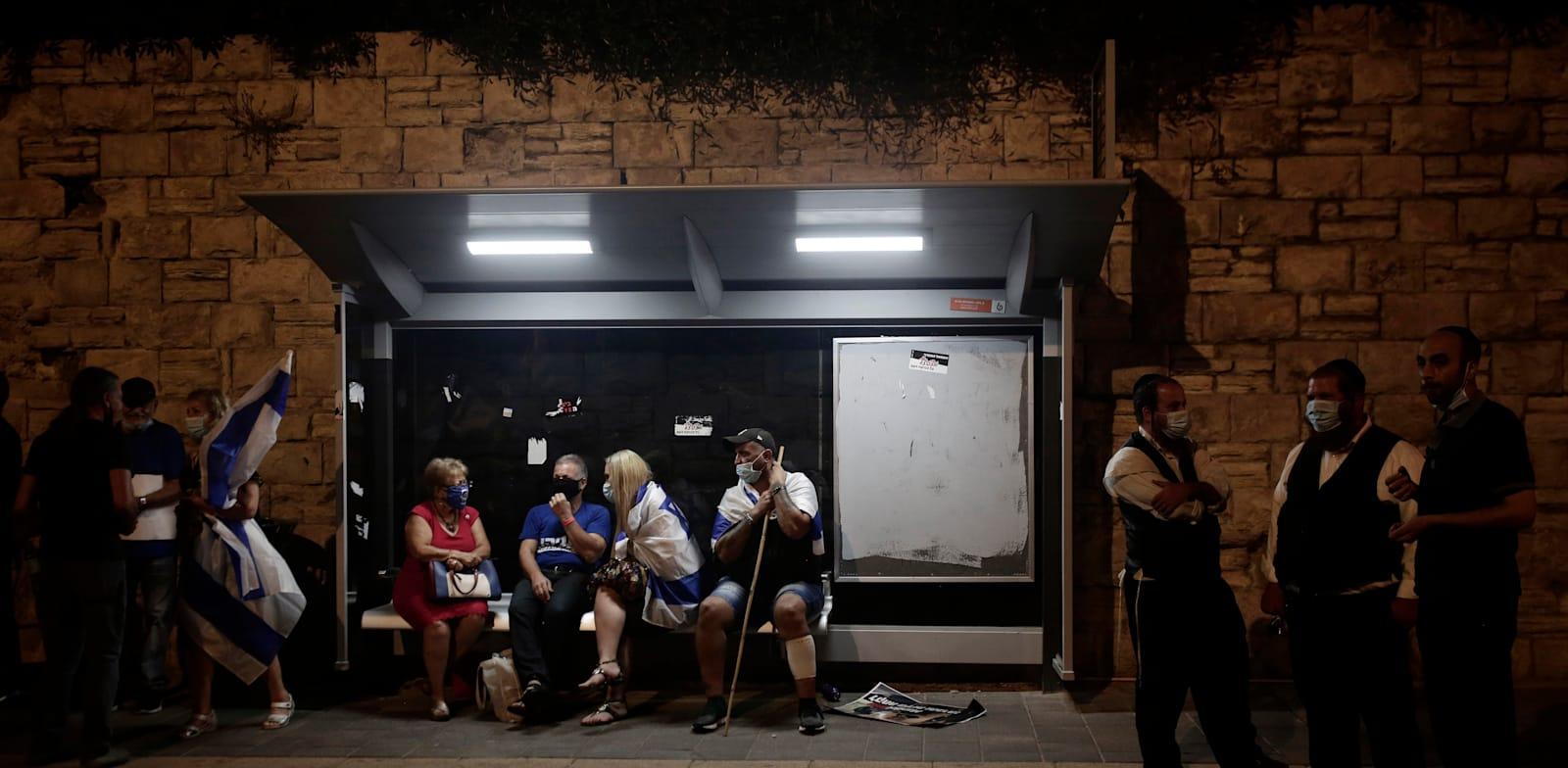 ממתינים בתחנת אוטובוס. לדברי המבקר, הסובסידיות גדלות ורמת השירות בירידה / צילום: Associated Press, Maya Alleruzzo