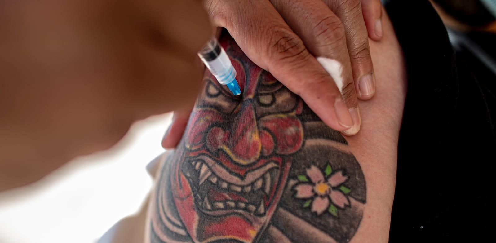אדם בצ'ילה מקבל את המנה השנייה של החיסון נגד קורונה של סינובאק / צילום: Associated Press, Esteban Felix
