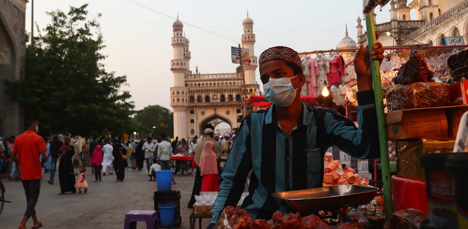 מוכר תמרים מול מסגד בהידראבאד, הודו / צילום: Associated Press, Mahesh Kumar A.