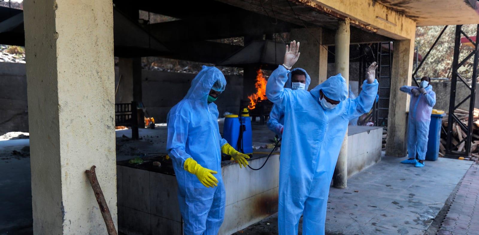צוות רפואי מחטא את עצמו  / צילום: Associated Press, Rafiq Maqbool
