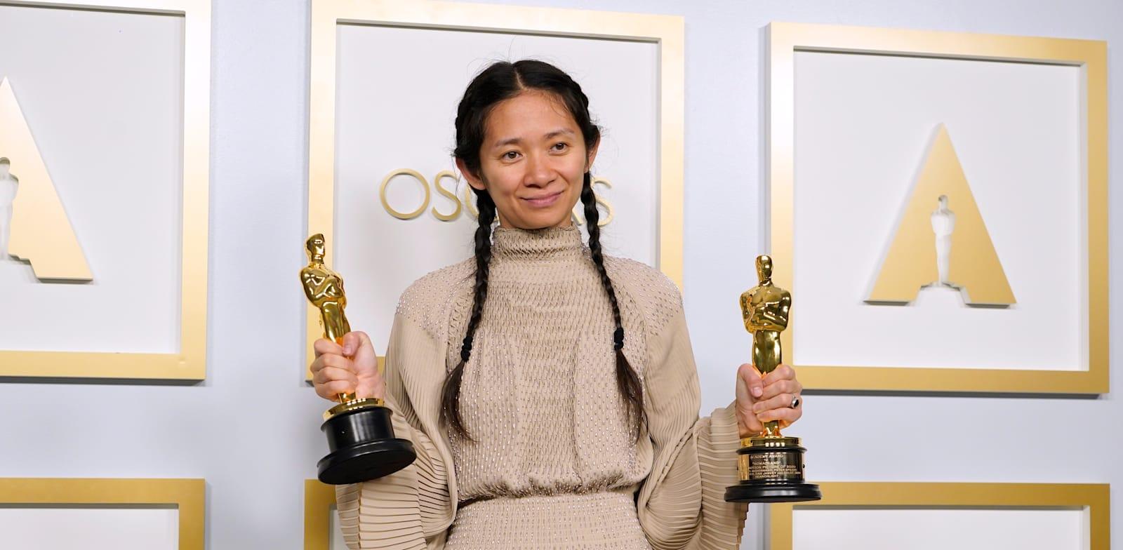 """הבמאית קלואי ז'או עם שני פרסי האוסקר שבהם זכתה על הסרט """"ארץ נוודים"""" / צילום: Associated Press, Chris Pizzello"""