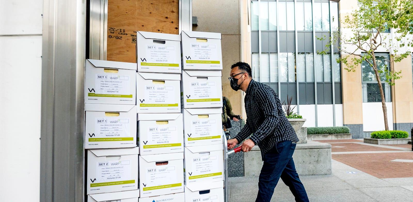 חבר בצוות עורכי הדין של אפל מוביל מסמכים לדיון בבית המשפט / צילום: Associated Press, Noah Berger