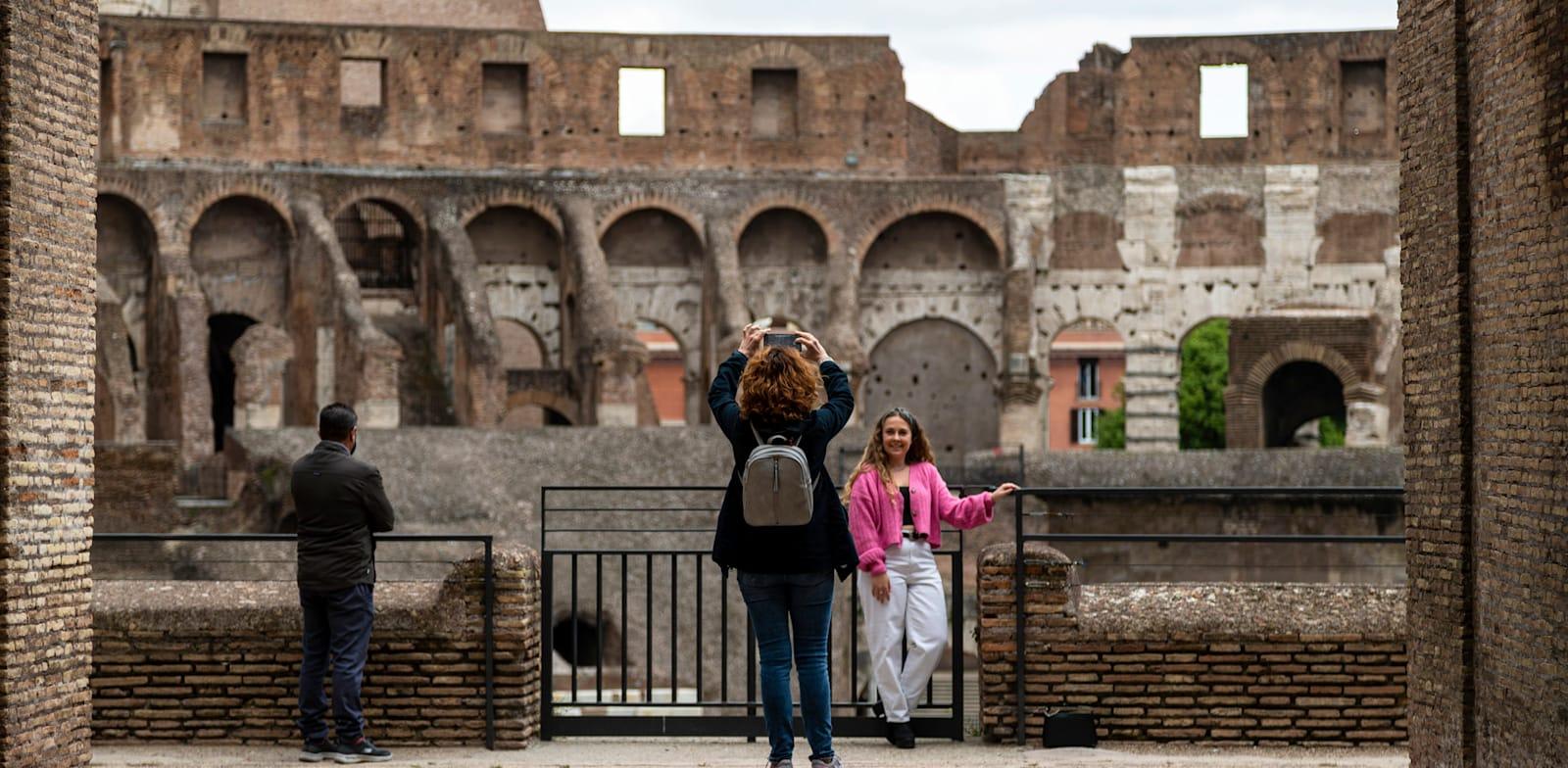 תיירים בקוליסאום ברומא. האתר נפתח מחדש בסוף אפריל / צילום: Associated Press, Domenico Stinellis