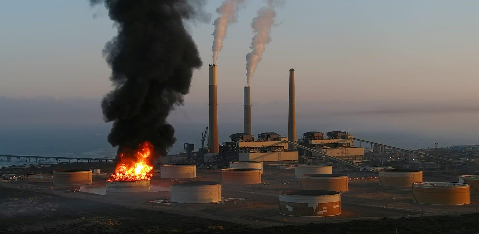 """שריפה במיכל דלק של חברת תש""""ן באשקלון שפרצה בעקבות פגיעה ישירה של רקטה / צילום: Reuters, Ilan Rosenberg"""