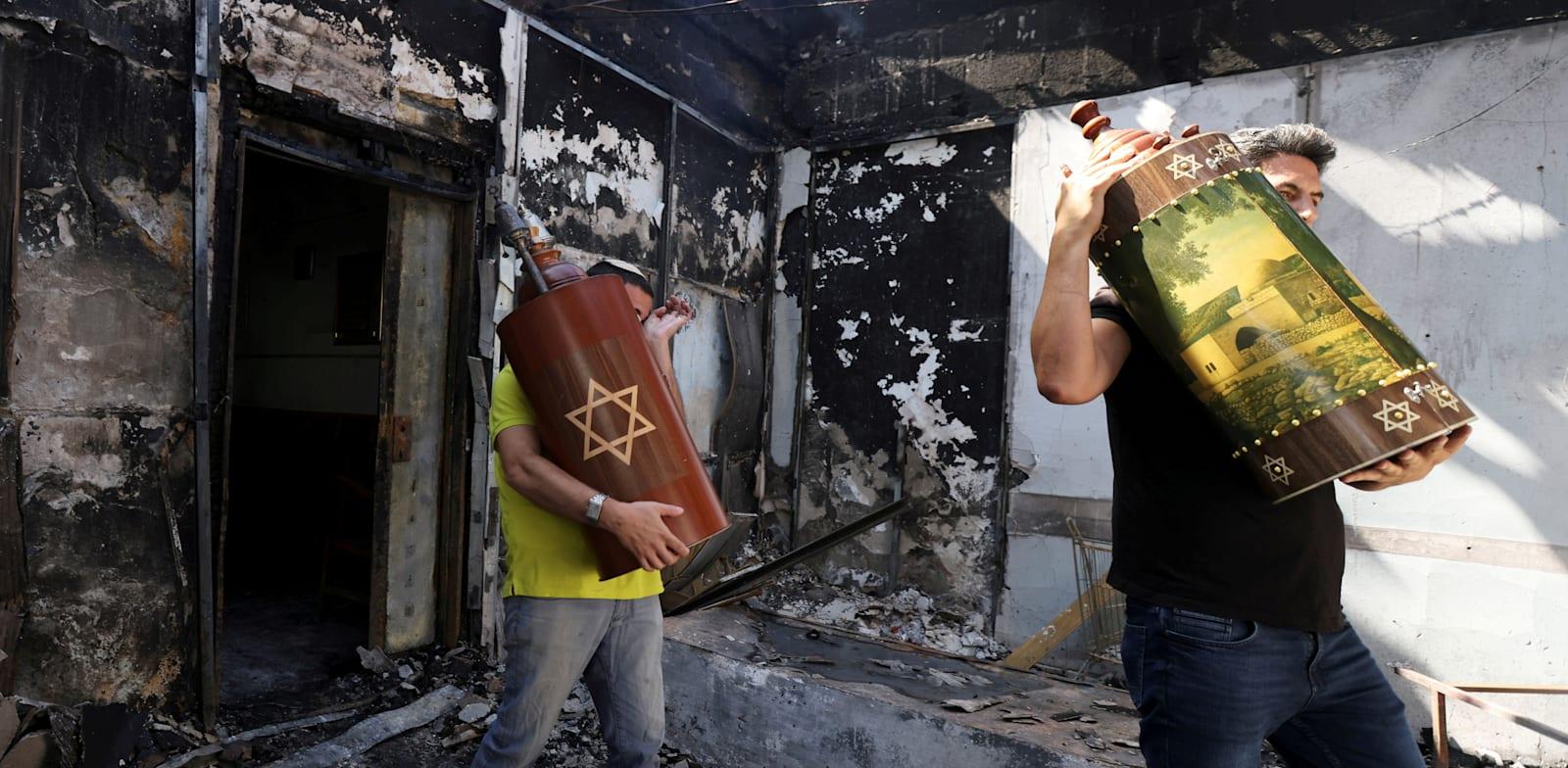 ספרי תורה מוצאים מתוך בית כנסת שנהרס בפרעות בלוד / צילום: Reuters, Ronen Zvulun