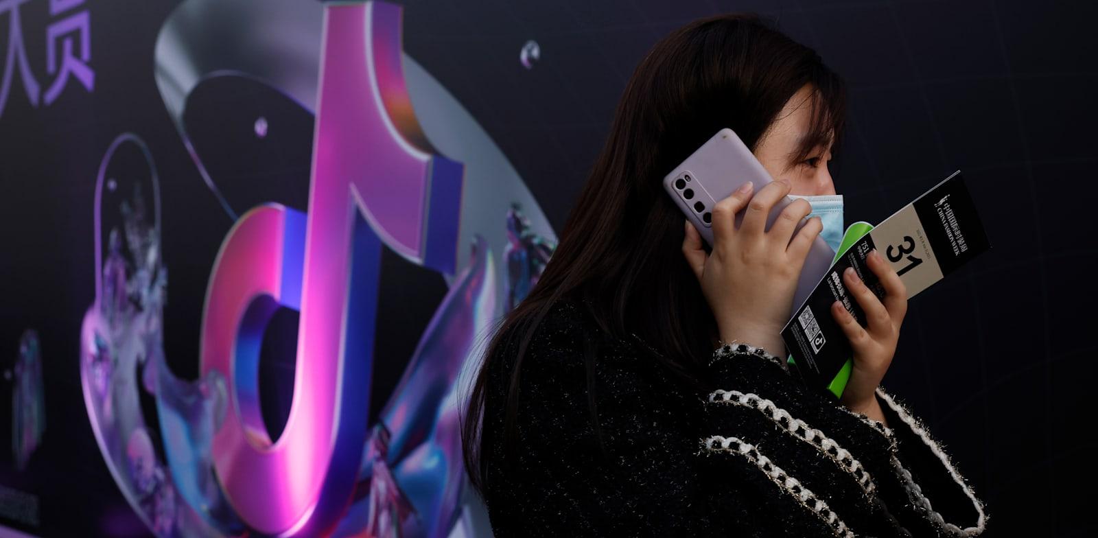 אישה משוחחת בטלפון ברחובות בייג'ינג / צילום: Associated Press, Ng Han Guan