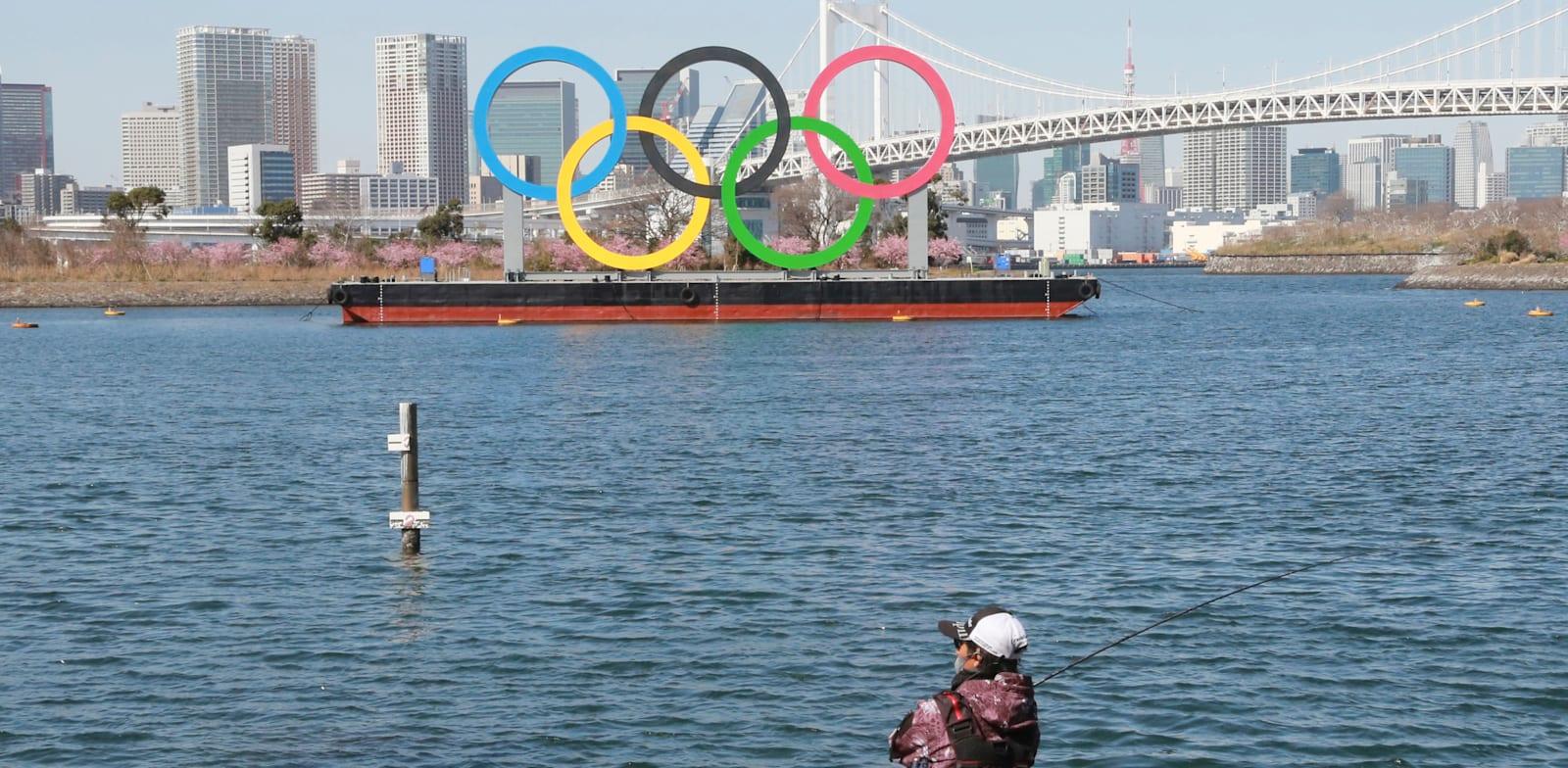 דייג יפני דג כשברקע סמל האולימפיאדה צף על גבי ספינה, השבוע / צילום: Associated Press, Koji Sasahara