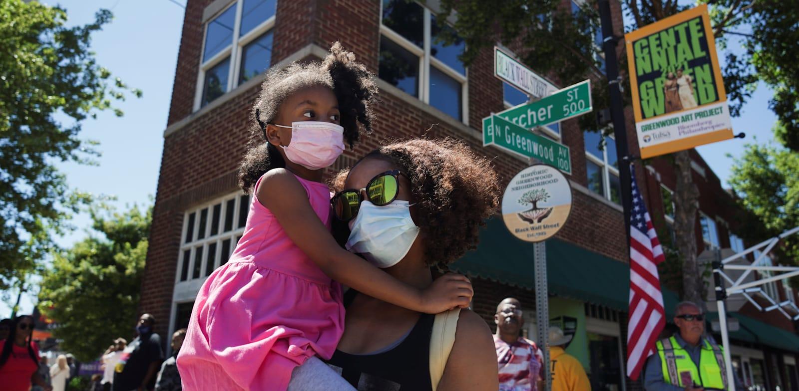 """אם ובתה עומדות ברחוב גרינווד לציון 100 שנה לטבח בטולסה, אירוע שגרם לפערי ענק בין החברה הלבנה לבין החברה השחורה בארה""""ב / צילום: Associated Press"""