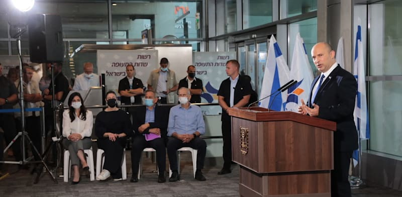 Prime Minister Naftali Bennett speaking at Ben Gurion Airport with ministers in background  credit: Yossi Zamir