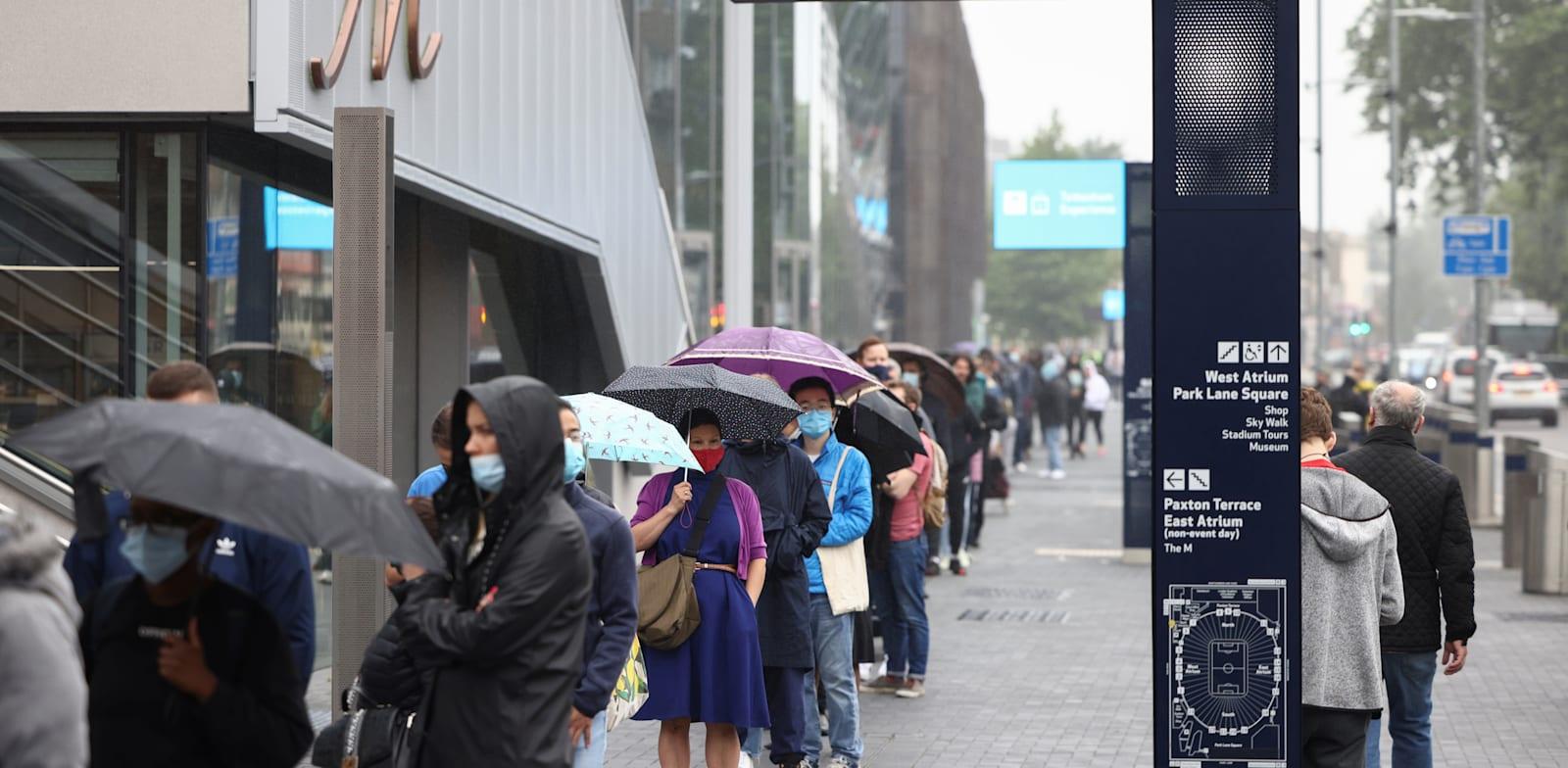 בריטניה: אנשים עומדים בתור מחוץ למרכז חיסוני קורונה / צילום: Reuters, HENRY NICHOLLS