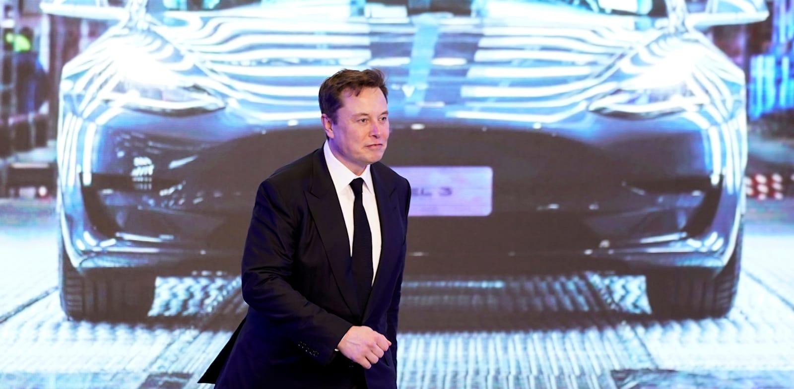 אלון מאסק על רקע מכונית טסלה 3 / צילום: Reuters, ALY SONG