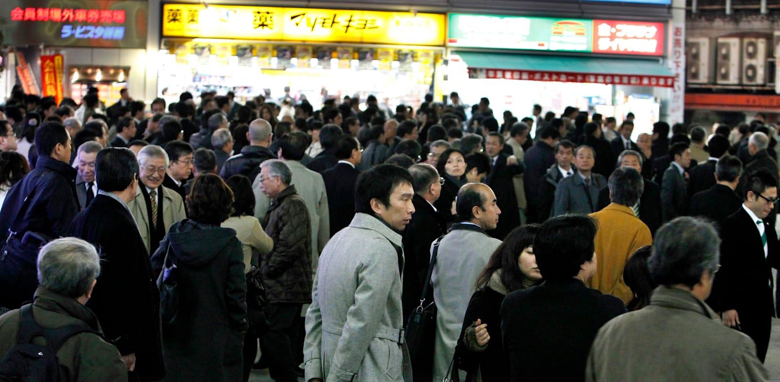 עובדי משרדים במרכז טוקיו בדרכם לתחנת הרכבת בתום  יום עבודה / צילום: Associated Press, Shizuo Kambayashi