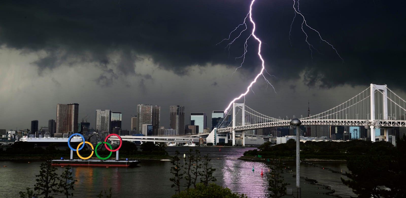 ברק בשמי טוקיו ליד סמל האולימפיאדה / צילום: Associated Press, Kyodo News
