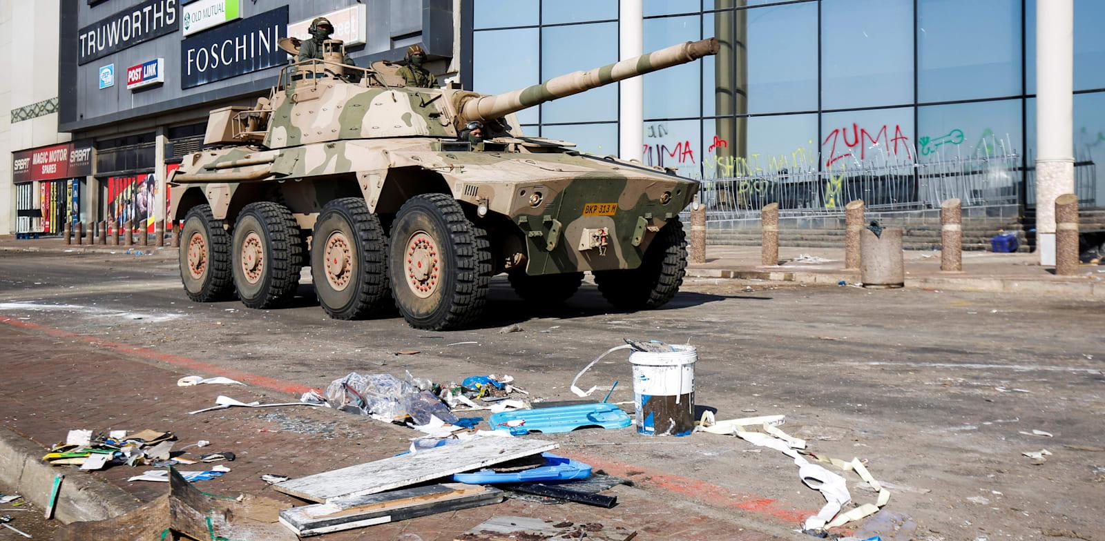 טנק של צבא דרום אפריקה מסייר ליד קניון וחנויות שנבזזו / צילום: Reuters