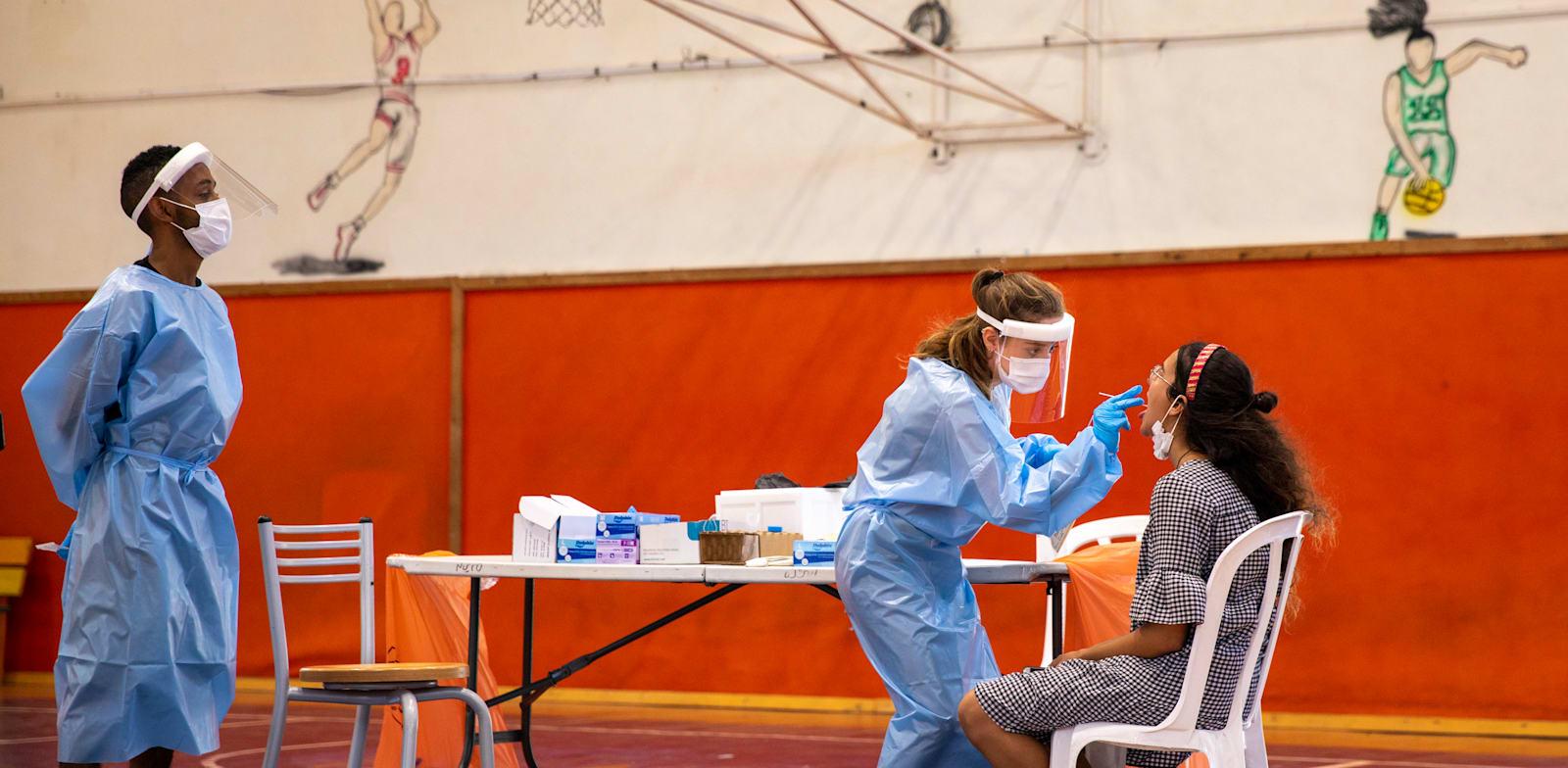 בדיקות קורונה לתלמידים בבית ספר בבנימינה ביוני האחרון / צילום: Associated Press, Ariel Schalit
