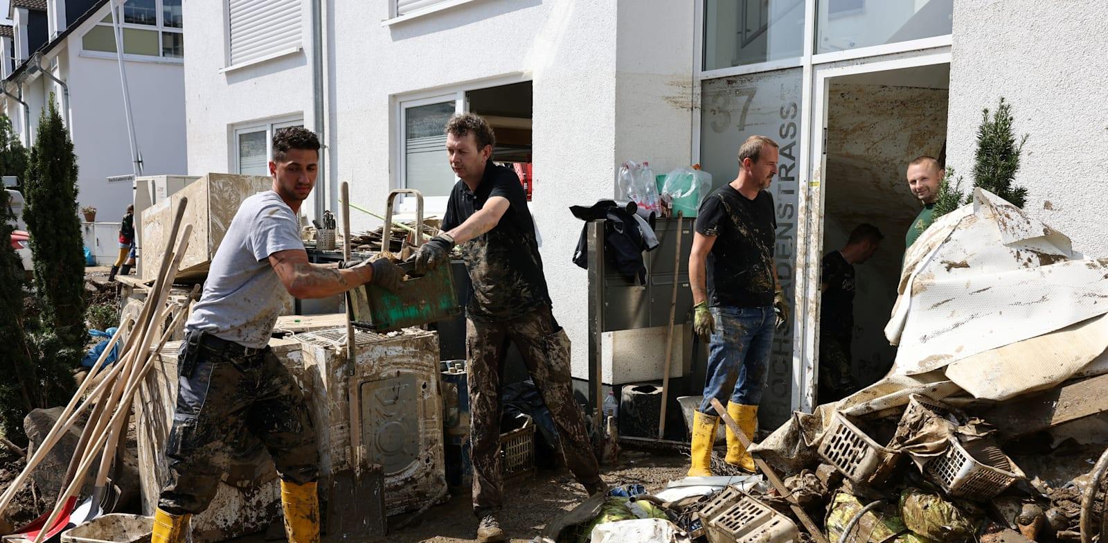 אנשים מפנים את ההריסות בעמק אהר בגרמניה, השבוע / צילום: Reuters, CHRISTIAN MANG