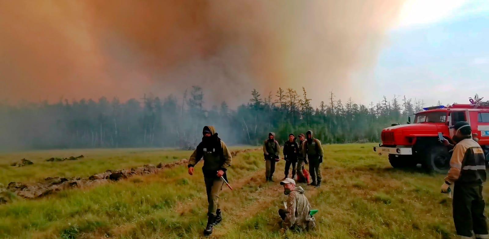 לוחמי האש פועלים בסיביר / צילום: Associated Press, Ivan Nikiforov
