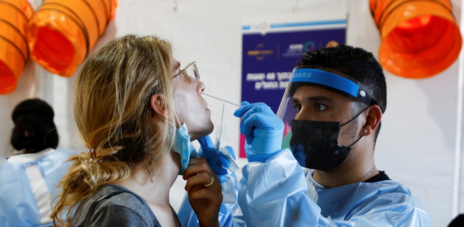 בדיקת קורונה באמצעות מטוש. רמת המהימנות בבדיקה ביתית של רניום היא 80% בלבד / צילום: Reuters, AMIR COHEN