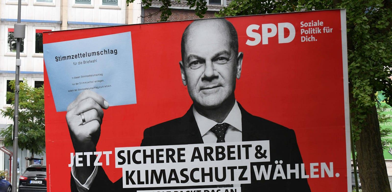 שלט של מועמד ה־SPD, אולף שולץ. ''הגיע הזמן לביטחון תעסוקתי והגנה על האקלים'' / צילום: Reuters, KH via www.imago-images.de