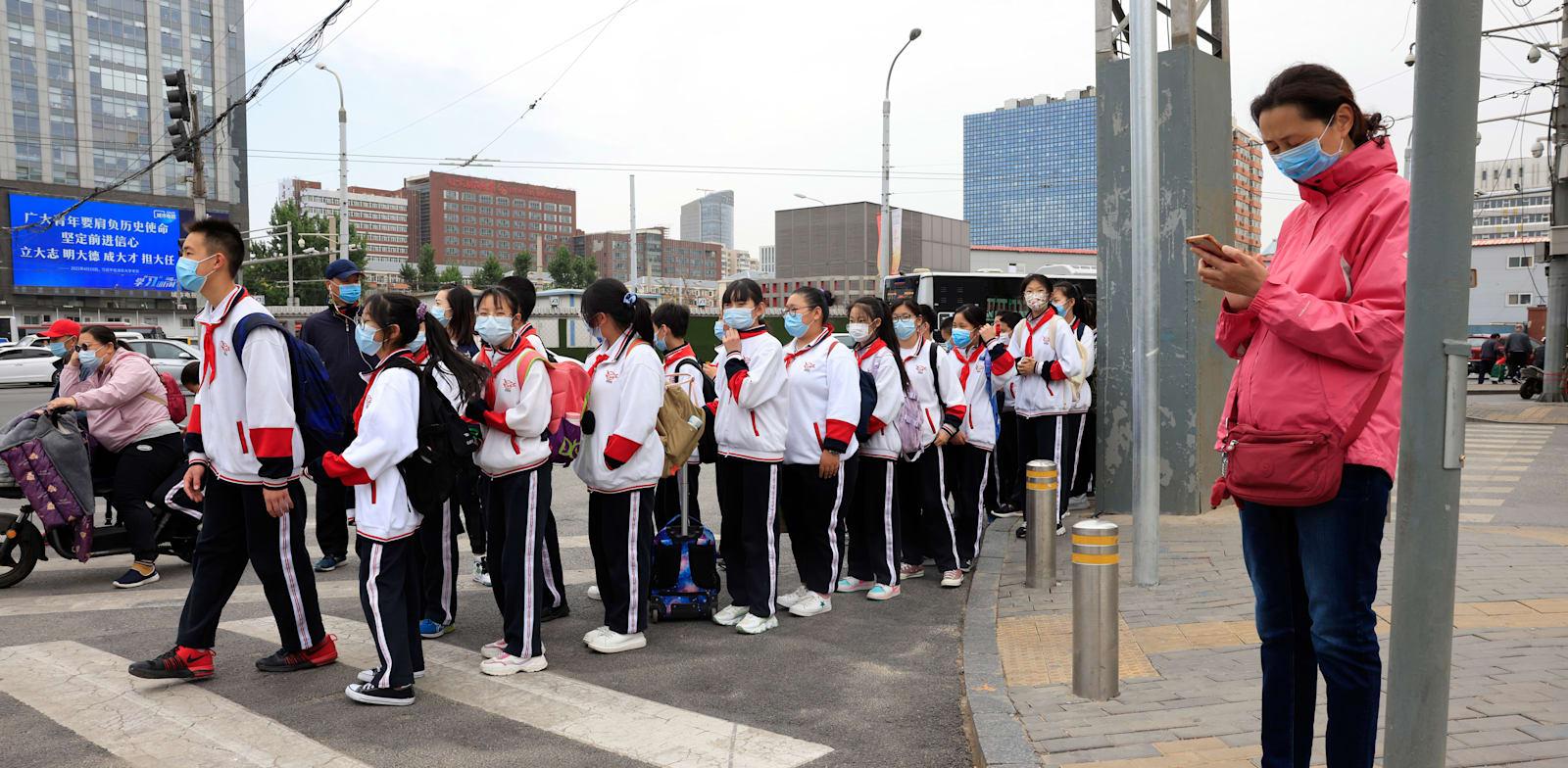 תלמידים בבייג'ין חוצים את הכביש בדרך לבית הספר / צילום: Associated Press, Ng Han Guan