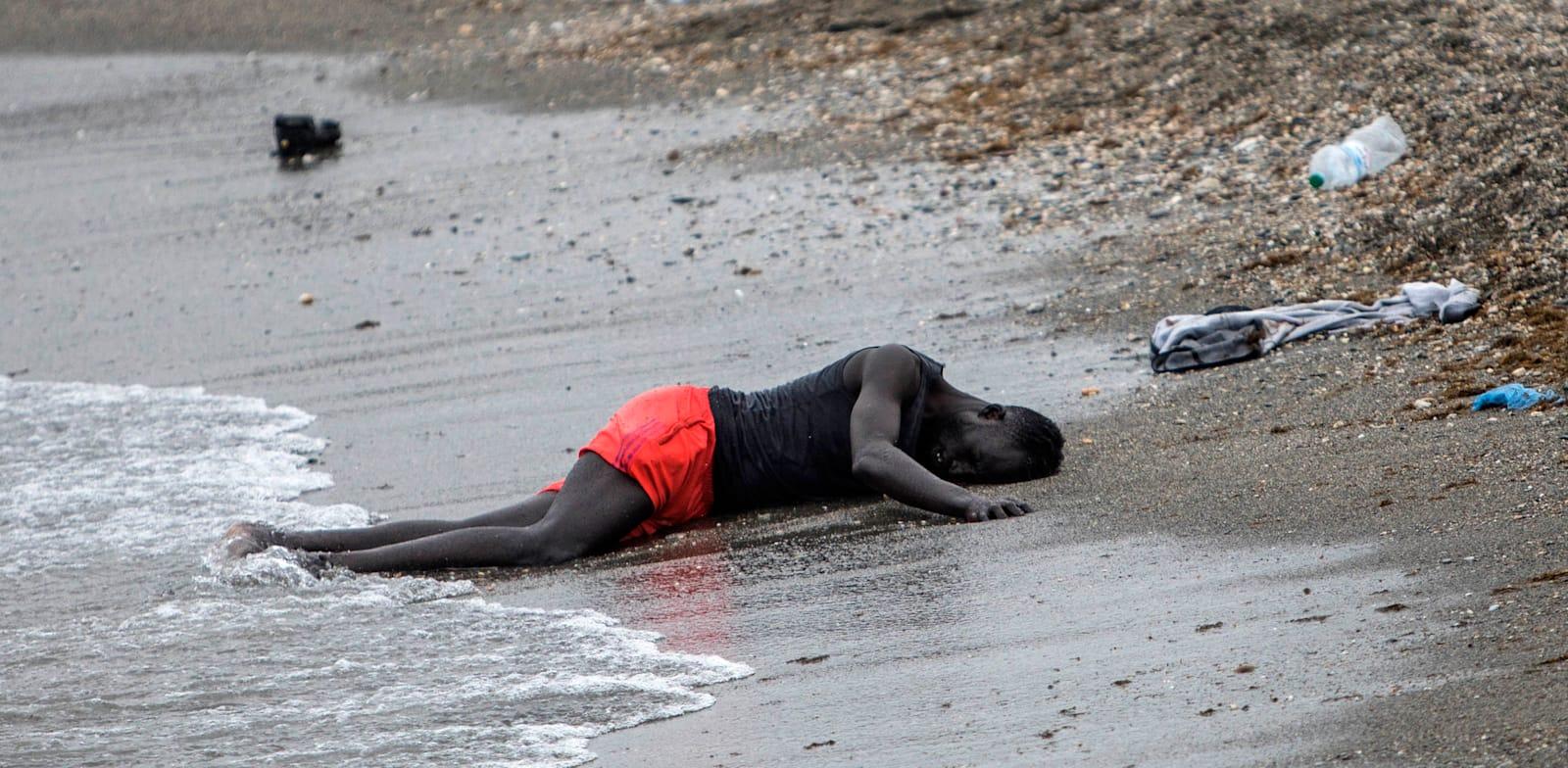 פליט מותש שוכב על החוף לאחר ששחה קילומטרים למובלעת הספרדית סאוטה בגבול מרוקו וספרד, מאי / צילום: Associated Press, Javier Fergo