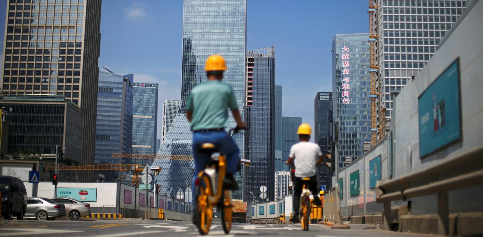 פועלי בניין רוכבים על אופניים בדרך לעבודה ליד מטה אוורגרנד בשנזן, ספטמבר / צילום: Reuters, CARLOS GARCIA RAWLINS