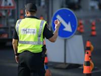 שוטר מפקח על עמידה בתקנות הקרורונה במחסום משטרתי / צילום: דוברות משטרת ישראל