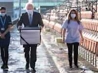 בוריס ג'ונסון מחזיק בקופסה עם חיסוני אסטרהזנקה במרכז חיסונים בלונדון / צילום: Reuters, Stefan Rousseau