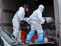 עובדים מעבירים גופה של אדם שמת מקורונה למשאית קירור לאחר שלא נשאר מקום בבית הלווית, ניו יורק באפריל 2020 / צילום: Associated Press, Craig Ruttle