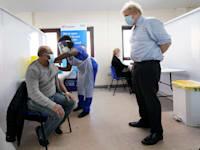 בוריס ג'ונסון, ראש ממשלת בריטניה, מתבונן בחיסון קורונה / צילום: Associated Press, Jon Super