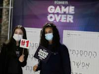צעירות מצטלמות עם שלטים במתחם חיסונים בחולון / צילום: Associated Press, Sebastian Scheiner