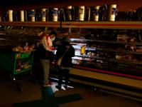 טקסנים משתמשים בפנס של הטלפון הסלולרי כדי לראות את המצרכים בחנות בדאלאס, בשבוע שעבר / צילום: Associated Press, LM Otero
