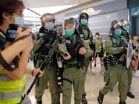 אנשי המשטרה בהונג קונג מנסים לעצור הפגנה של אנשי תקשורת לציון שנה להתקפת המפגינים ברכבת התחתית / צילום: Associated Press, Kin Cheung