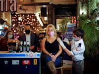 """אישה מקבלת חיסון לקורונה בפאב, כחלק מיוזמה של עיריית ת""""א שמציעה משקה לכל מתחסן / צילום: Reuters, Corinna Kern"""