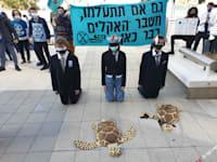 """פעילי """"המרד בהכחדה"""" מוחים מול משרדי מנורה על השקעות בחברות דלקים מאובנים / צילום: מישל פסטרנק"""