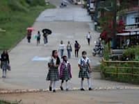 תלמידות בקולומביה בדרכן לבית הספר היחיד באזור המגורים שלהן שעדיין פתוח בצל הקורונה / צילום: Associated Press, Fernando Vergara