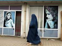 אישה בבורקה עוברת מול מכון יופי / צילום: Associated Press, Allauddin Khan