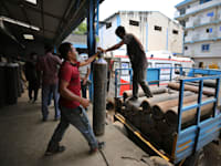 בלוני חמצן הנשלחים לבתי החולים בהודו. אחת מכל 5 בדיקות במדינה היא חיובית / צילום: Associated Press, Aijaz Rahi