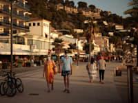 עוברי אורח מטיילים בטיילת באי מיורקה / צילום: Associated Press, Joan Mateu