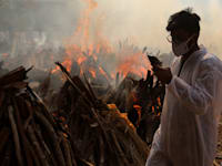 בן משפחה של אחד ממתי הקורונה ליד המדורות שבהן שורפים את הגופות בניו דלהי, השבוע / צילום: Reuters, SOPA Images