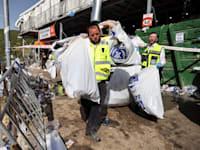 """עובד זק""""א סוחב שקיות מלאות כובעים לאחר האירוע בהר מירון / צילום: Reuters, מירון"""