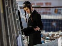 צעיר מהחברה החרדית מאתר חפצים בזירת האסון בהר מירון / צילום: Reuters, Ilia Yefimovich
