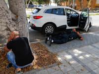 תושבים באשקלון תופסים מחסה בזמן נפילת הרקטות / צילום: Associated Press, Ariel Schalit