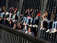 צעירים גרמנים נהנים מהשמש על הגשר האקר־בריקה במינכן, בחודש מרץ / צילום: Associated Press, Matthias Schrader