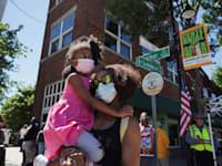 """אמא עומדת עם בתה ברחוב גרינווד לציון 100 שנה לטבח בטולסה, אירוע שגרם לפערי ענק בין החברה הלבנה לבין החברה השחורה בארה""""ב / צילום: Associated Press"""