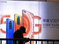 אדם עובר ליד שלט חוצות של סמארטפון 5G של וואווי / צילום: Associated Press, Ng Han Guan